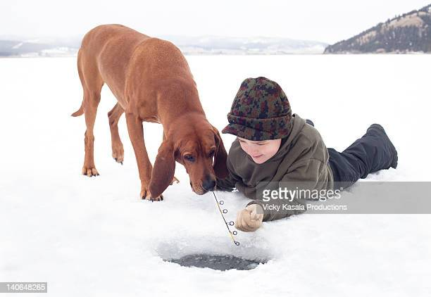 Young boy with his Coon hound dog ice fishing.