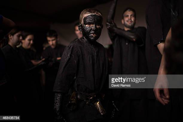 Young boy with his face covered in oil and soot as he dresses up as a devil to join a carnival festival on February 14, 2015 in Luzon, Spain. Every...