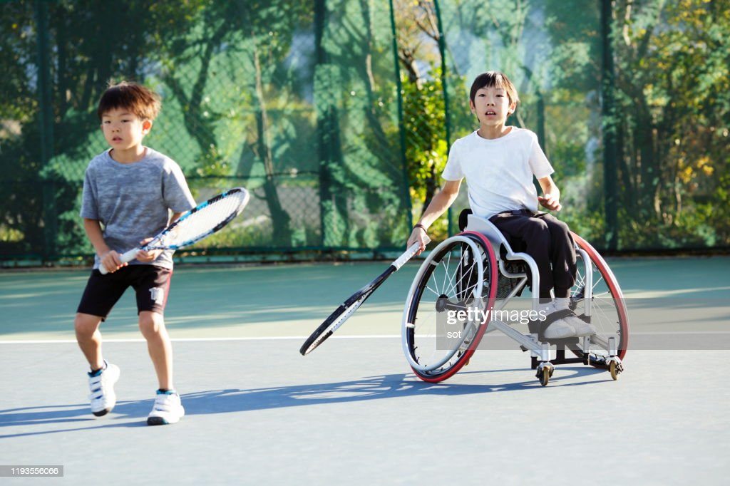 Young boy with his older brother on a wheelchair playing tennis together on a tennis court : ストックフォト