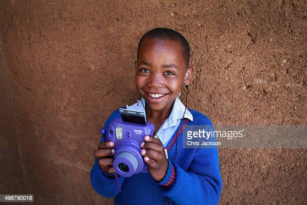 A young boy with impaired hearing takes photographs on a Fuji instant camera duirng a community camp at the new Mamohato Children's Centre on October...