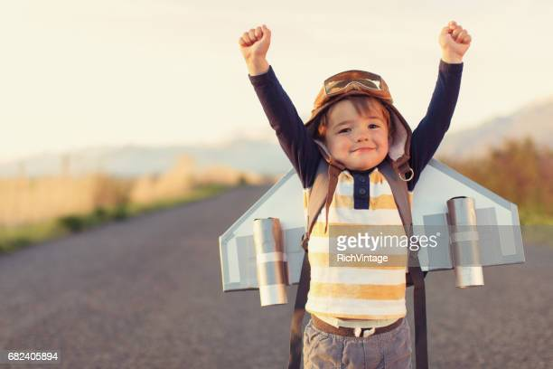 young boy with jet pack with arms raised - wishing stock pictures, royalty-free photos & images