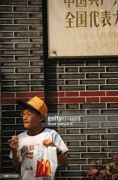 young boy with mcdonald's bag under plaque commemorating first national congress of the chinese communist party. - mcdonald's stock pictures, royalty-free photos & images