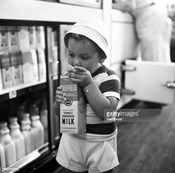 A young boy with milk dribbling down his arm drinks from a carton of milk while standing in a store aisle New York 1949
