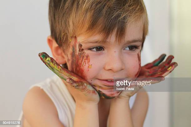 Young boy with painted face and hands