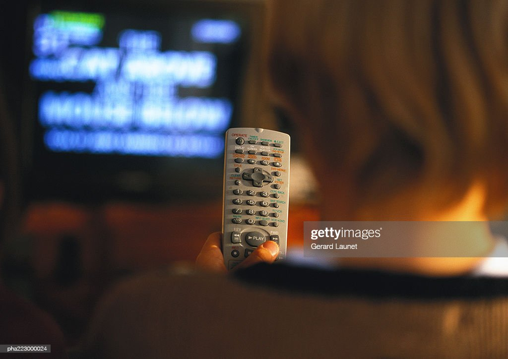 Young boy with remote in his hand watching TV, view from behind, close up, blurred. : Stockfoto