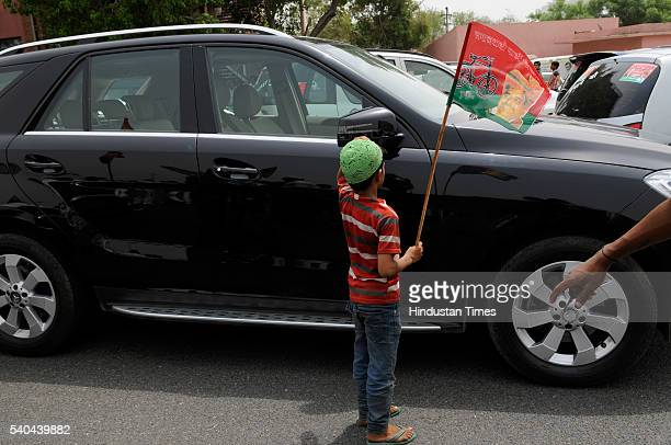 Young boy with Samajwadi Party flags as large number of party workers gathered to welcome newly elected Rajya Sabha MP Surendra Singh Nagar at DND...