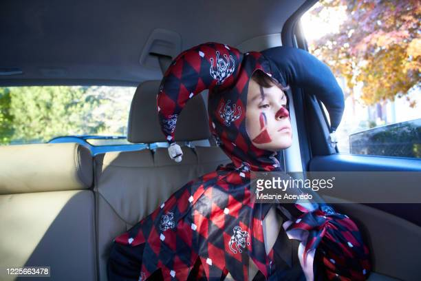 young boy with short brown curly hair and brown eyes close up holding small stuffed panda toy boy is sitting in the backseat of car looking outside of car window wearing a halloween costume