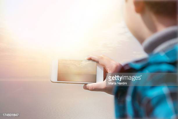 Young boy with smartphone at sunset