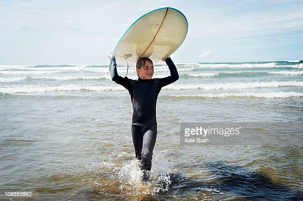 Young boy with surf board on his head