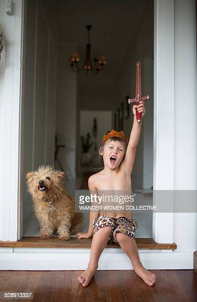 Young boy with sword and crown at home with dog