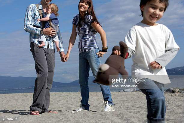 young boy (3-4 years) with teddy bear, parents with baby (6-9 months) in background on beach - 25 29 years stock pictures, royalty-free photos & images