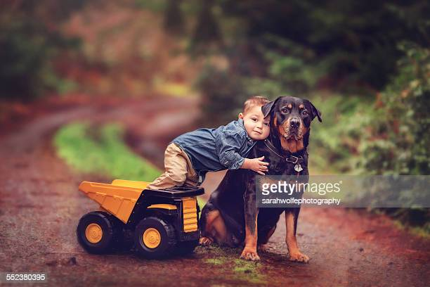 Young boy with toy truck and rottweiler