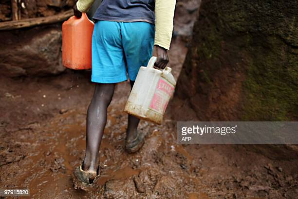 A young boy with two empty jerry cans searches for water in Kibera the second biggest slum in Africa that is home to about 800000 people in Nairobi...