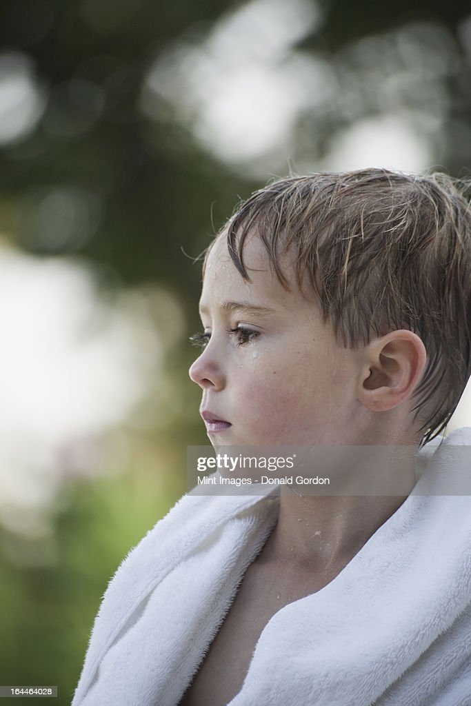 A young boy with wet hair, wrapped in a towel after swimming. : Stock Photo