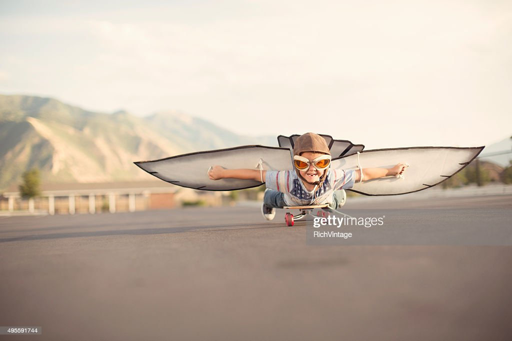 Young Boy with Wings Flies On Skateboard : Stock Photo