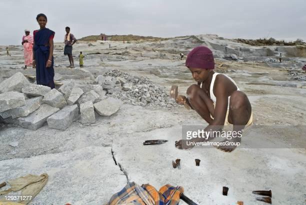 Young boy worker in granite quarry preparing rock slab for splitting Nandi hills Kolar distict Karnataka India