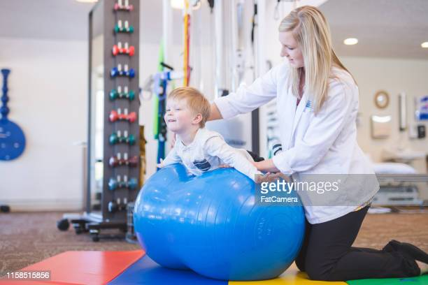 young boy working with a physical therapist at a clinic - pediatrician stock pictures, royalty-free photos & images