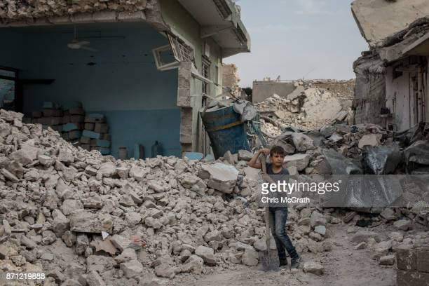 A young boy works to clear rubble from in front of his house in an outer neighborhood of the Old City in West Mosul on November 6 2017 in Mosul Iraq...