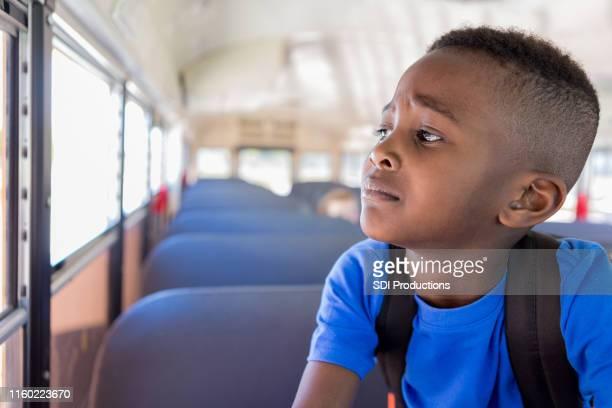 junge schaut besorgt aus busfenster - schulkind nur jungen stock-fotos und bilder