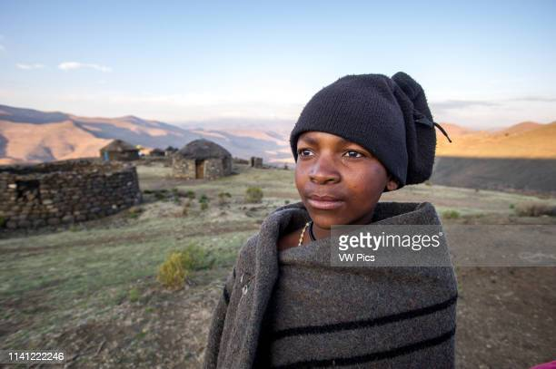 Young boy wrapped in a blanket standing in front of a stone hut in Lesotho Africa