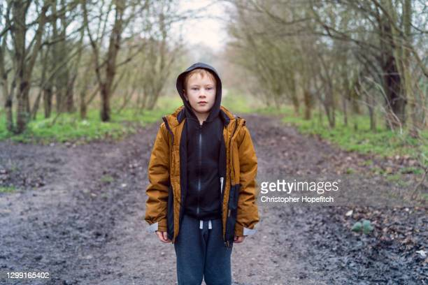 a young boy wrapped up warm standing in the middle of a footpath - woodland stock pictures, royalty-free photos & images