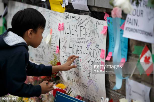 A young boy writes a message at a memorial for victims of the mass killing on Yonge Street at Finch Avenue on April 24 2018 in Toronto Canada A...