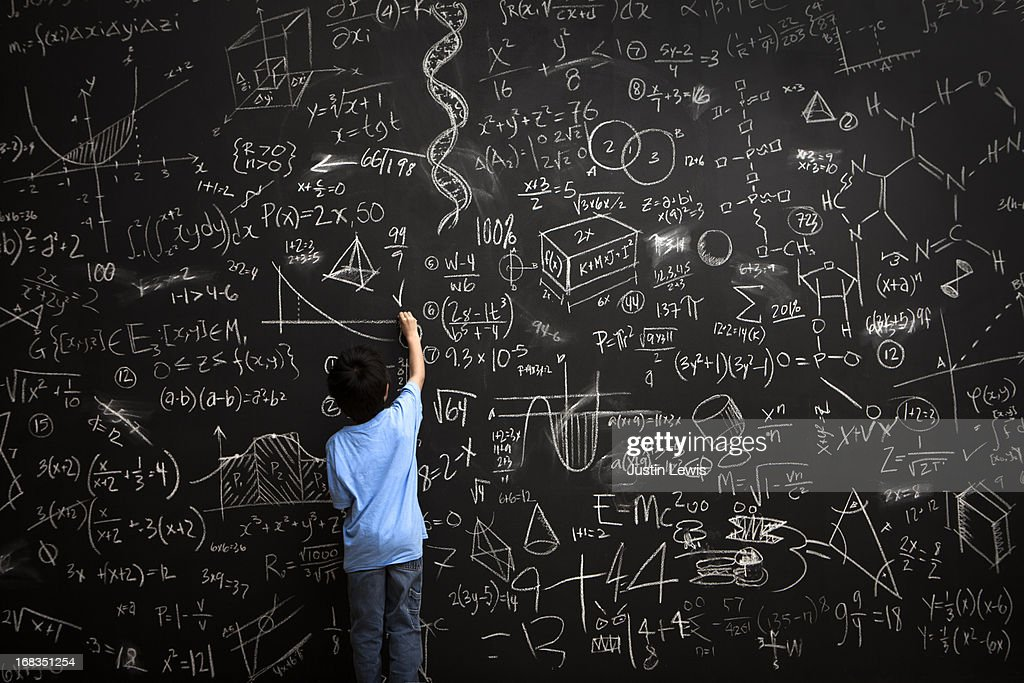 Young boy writes math equations on chalkboard : Foto de stock