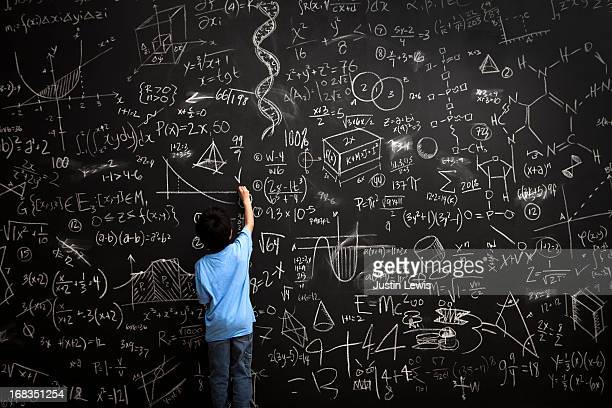 Young boy writes math equations on chalkboard