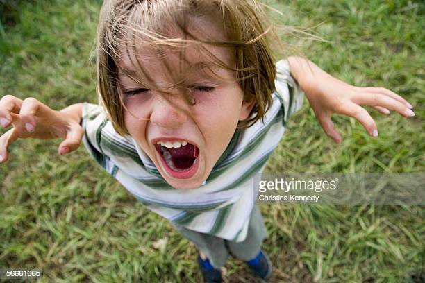 a young boy yelling outdoors - christina luft stock-fotos und bilder