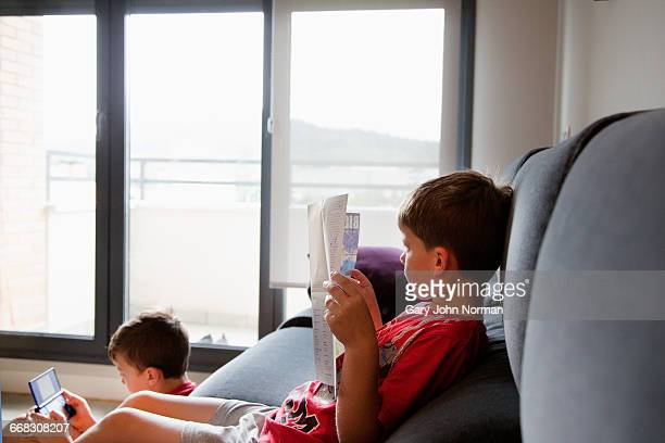 young boys 8-10 years relaxing on sofa at home - 8 9 years stock pictures, royalty-free photos & images