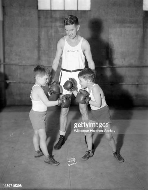Young boys Alec and Bobby McCormick pose as boxers in front of John Walsh University of Wisconsin boxing coach Madison Wisconsin January 15 1934