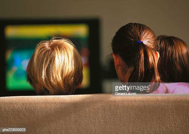 Young boys and girl sitting on couch watching TV.