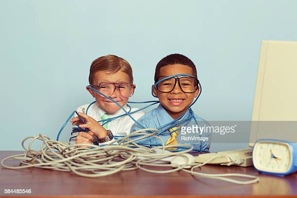 Young Boys and IT Professionals Smile at Computer Desk
