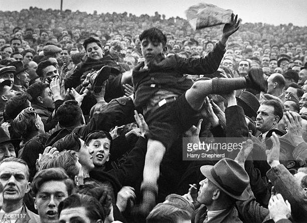 Young boys are passed over the heads of a football crowd to the front so that they can see the match between Arsenal and Chelsea at Stamford Bridge