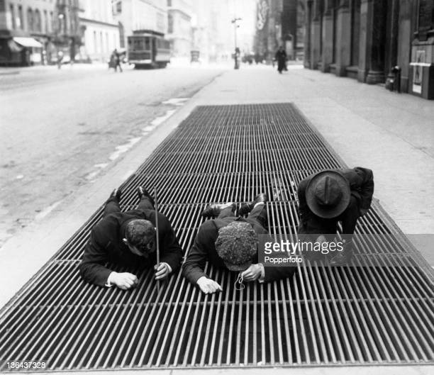 Young boys attempting to retrieve lost coins through street grating during the Depression in New York USA circa 1930