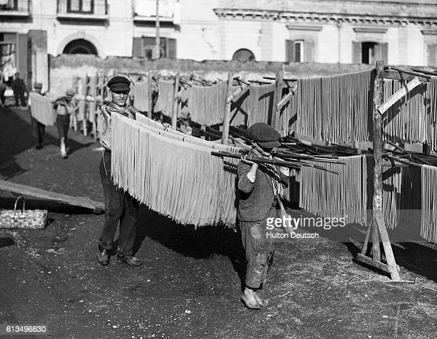 Young boys carry poles of spaghetti into a factory yard for drying