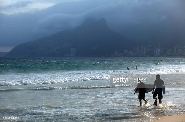 Young boys carry their surfboards on Ipanema Beach as the 2014 FIFA World Cup nears on June 9 2014 in Rio de Janeiro Brazil
