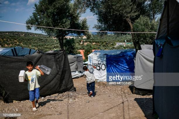 Young boys carry water bottles at a camp outside the Moria refugee camp in the island of Lesbos on August 5 2018