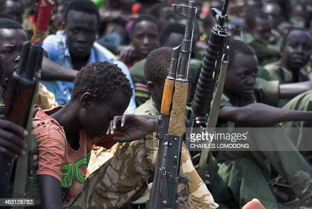 Young boys children soldiers sit on February 10 2015 with their rifles at a ceremony of the child soldiers disarmament demobilisation and...