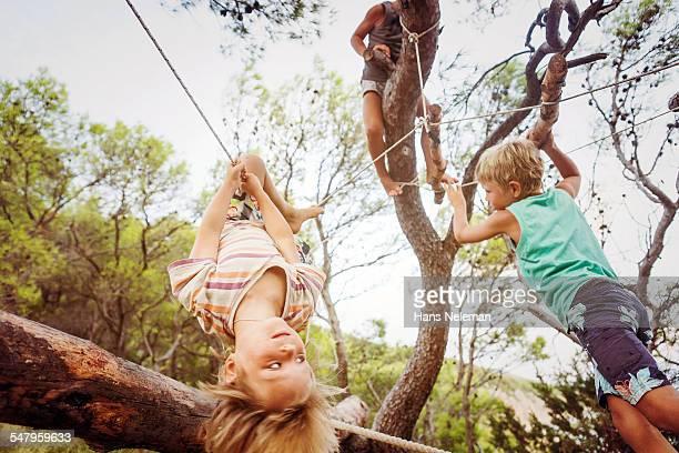 Young boys climbing across a ropes course