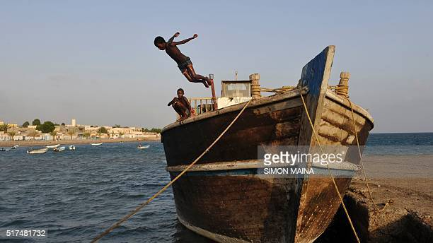 Young boys dive into the sea from a boat on March 25 2016 in Tadjoura north central Djibouti / AFP / SIMON MAINA