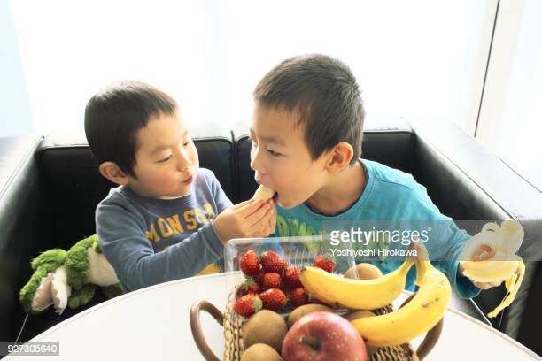 young boys eat bananas with family at home - 兄弟 ストックフォトと画像