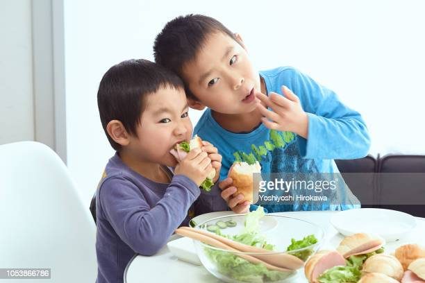 young boys eating breakfast with family in home - 兄弟 ストックフォトと画像