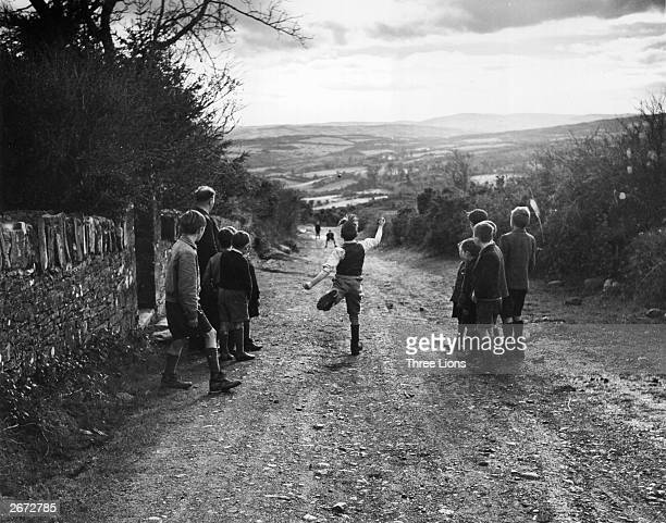 Young boys enjoy a game of road bowling in an Irish country lane