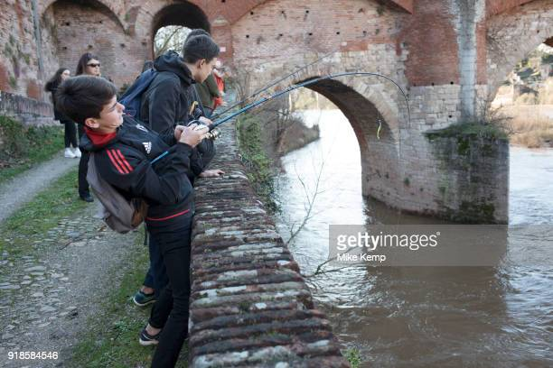 Young boys fishing along the Tarn River in Albi Southern France With his fishing rod bending this boy had caught something way bigger than he had...