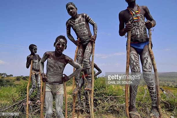 Young boys from the Mursi tribe walk on stilts in Ethiopia's southern Omo Valley region near Jinka on September 22 2016 The Mursi are a Nilotic...