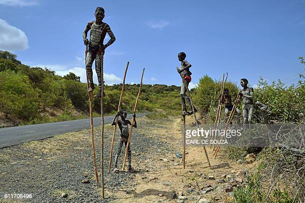 TOPSHOT Young boys from the Mursi tribe walk on stilts in Ethiopia's southern Omo Valley region near Jinka on September 22 2016 The Mursi are a...