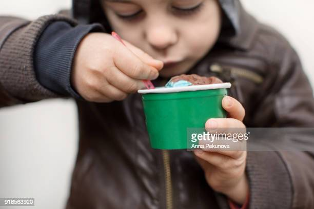 Young boy's hands holding ice-cream while eating
