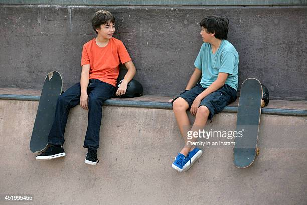 Young boys hanging out at skateboard park.