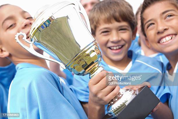 Young boys happily holding winning trophy